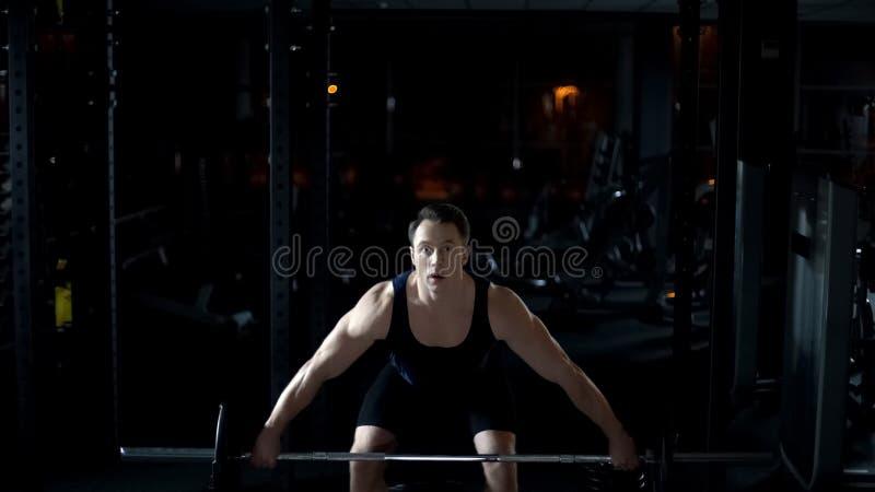 Le bodybuilder fort soulève facilement le barbell lourd, formant le programme de séance d'entraînement photo libre de droits
