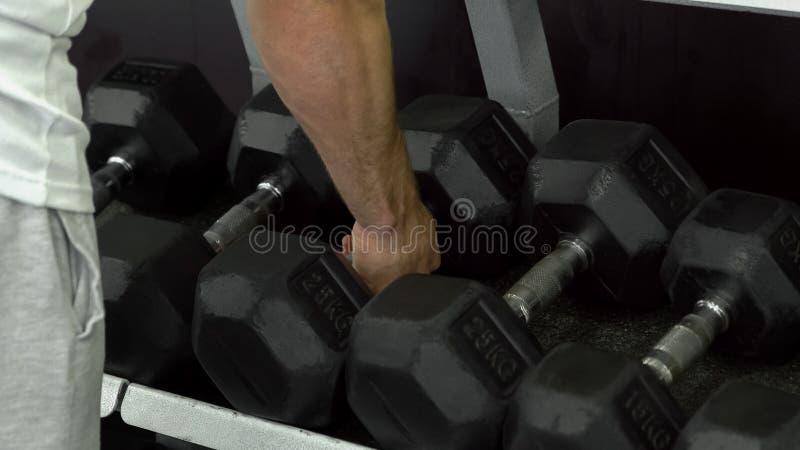 Le Bodybuilder prend une haltère haut étroit de mains d'homme Formation de poids d'homme dans le gymnase image stock