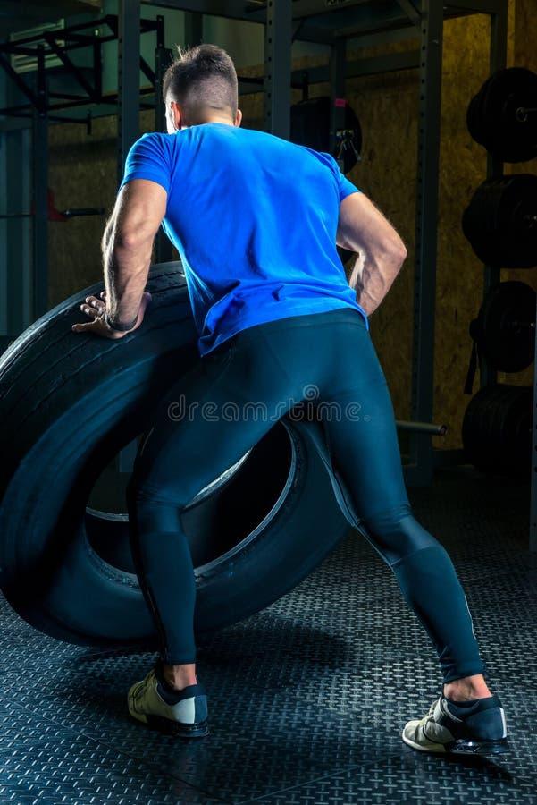 Le Bodybuilder s'exerce dans le gymnase avec une roue lourde, la vue franc image stock