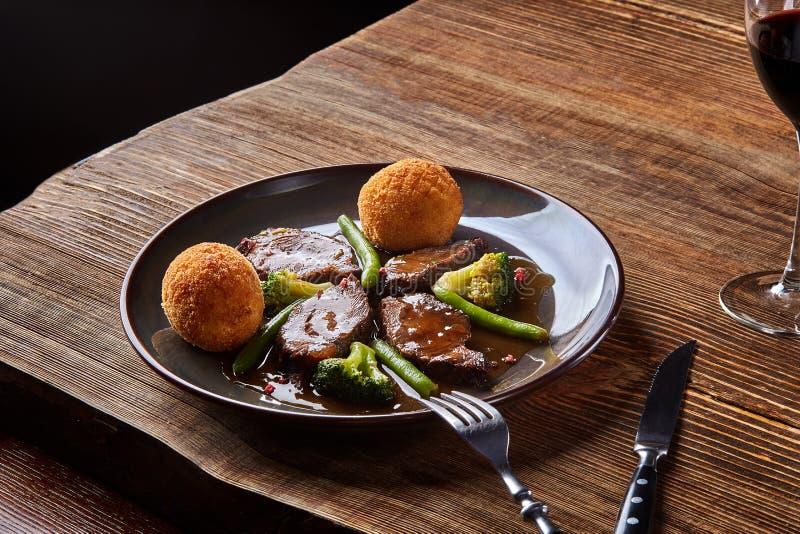 Le boeuf cuit avec des légumes et un verre de vin sec rouge sur la table en bois, se ferment  Paraboloïdes chauds de viande image stock