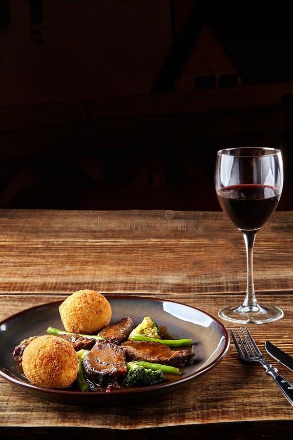Le boeuf cuit avec des légumes et un verre de vin sec rouge sur la table en bois, se ferment  Paraboloïdes chauds de viande photo stock