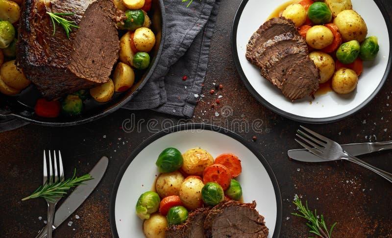 Le boeuf de rôti coupé en tranches avec du miel a glacé des légumes, servis du plat Dîner de fête photo stock