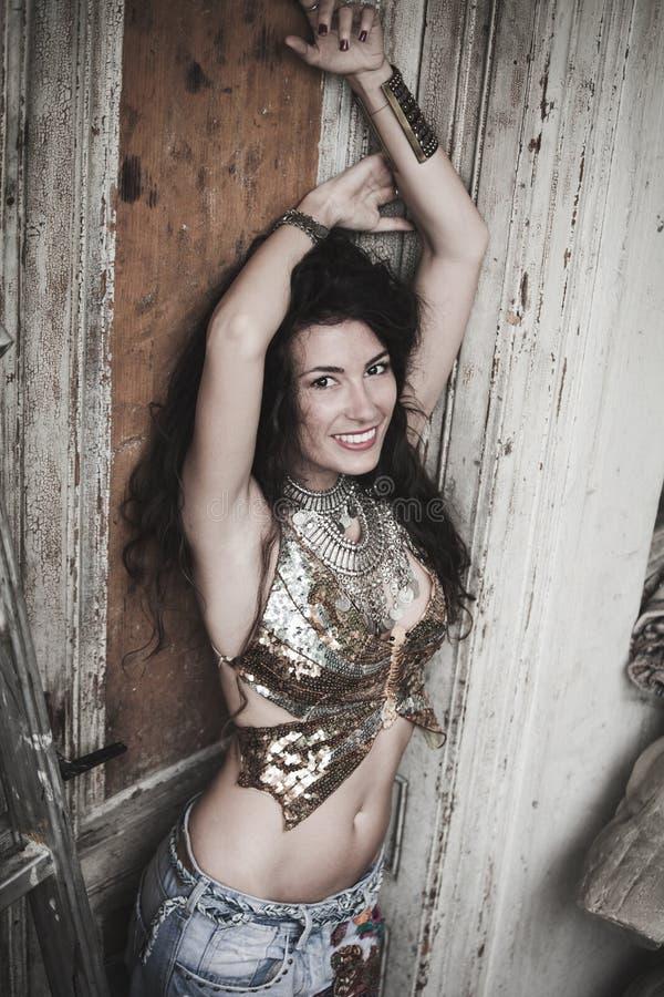 Le boho de sourire dénomment la fille extérieure dans la porte en bois avant photographie stock libre de droits