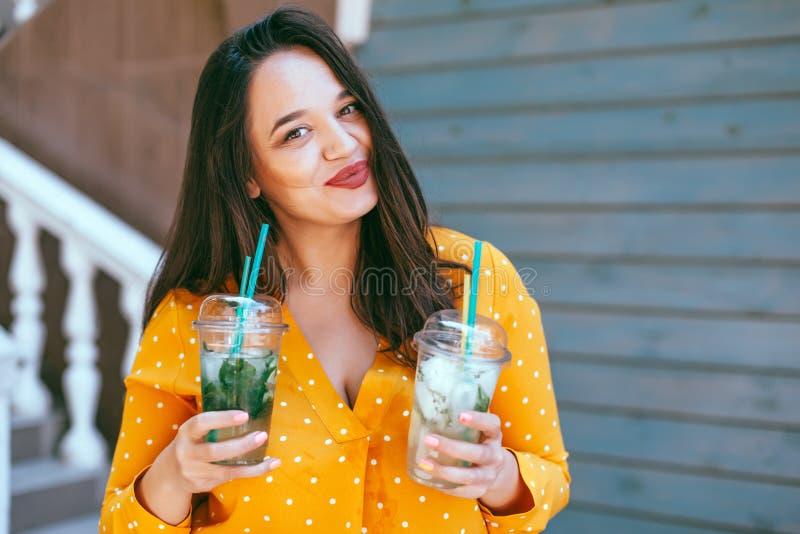Le boire plus de femme de taille emportent le cocktail au-dessus du mur de café de ville photographie stock libre de droits