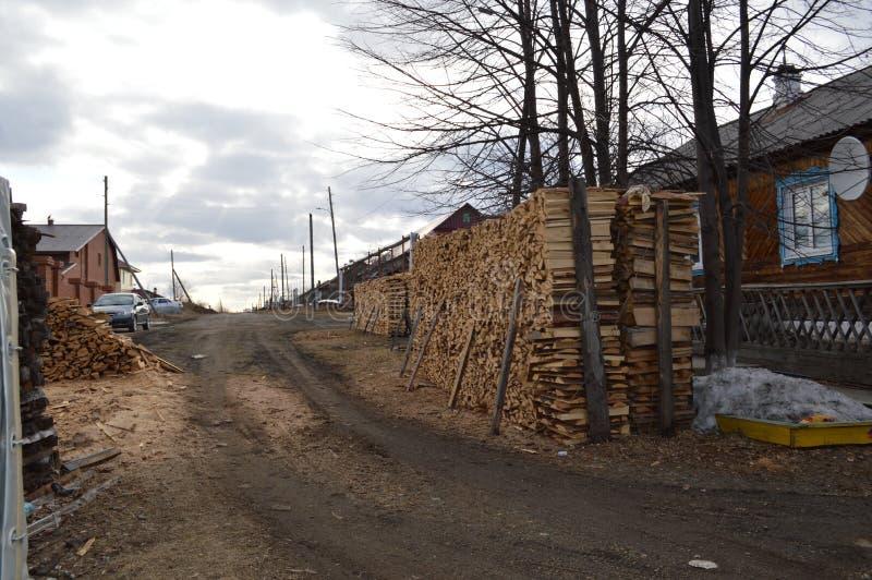Le bois de chauffage empilé dans un tas de bois a scié le bois de chauffage en bois de rondin pour moissonner image libre de droits