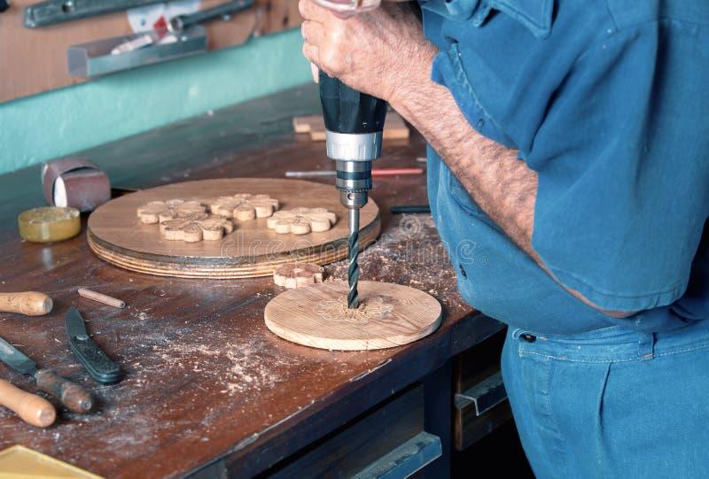 Le bois de perçage d'ébéniste avec une puissance forent dedans l'établi photos libres de droits