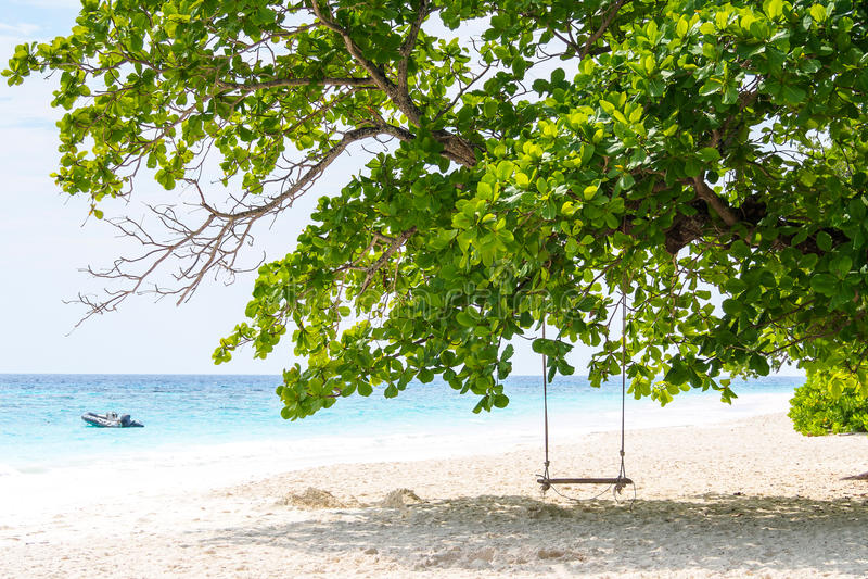 Le bois et la robe longue intéressants d'oscillation sous le grand arbre sur le sable échouent avec le bateau et le ciel bleu à l photographie stock