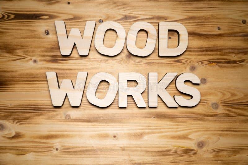 Le bois fonctionne des mots faits de caractères gras en bois sur le conseil en bois photo libre de droits