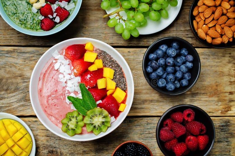 Le bol de petit déjeuner de smoothies de fraise avec la noix de coco s'écaille, mangue, photos libres de droits
