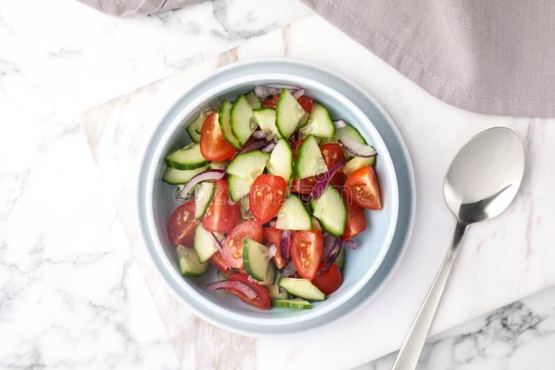 Le bol de salade v?g?tarienne avec le concombre, la tomate et l'oignon a servi sur la table image stock