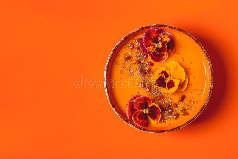 Le bol de Smoothie avec la pensée comestible fleurit, des graines de chia, berrie de goji photographie stock