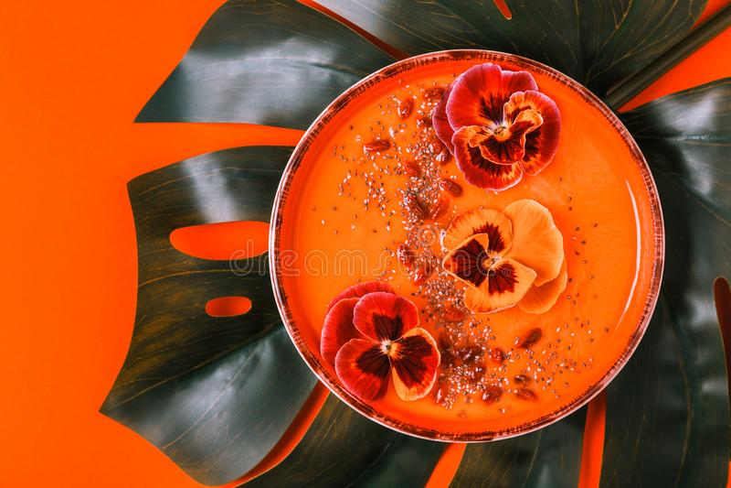 Le bol de Smoothie avec la pensée comestible fleurit, des graines de chia, berrie de goji photo libre de droits