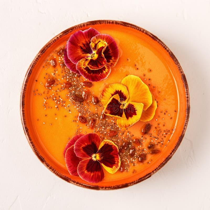 Le bol de Smoothie avec la pensée comestible fleurit, des graines de chia, berrie de goji photos stock