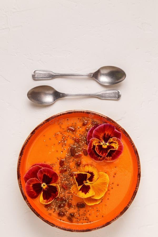 Le bol de Smoothie avec la pensée comestible fleurit, des graines de chia, berrie de goji image libre de droits