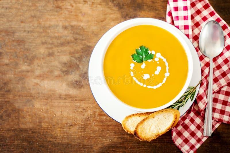 Le bol de soupe jaune végétale avec le persil et les croûtons plus de courtisent photos stock