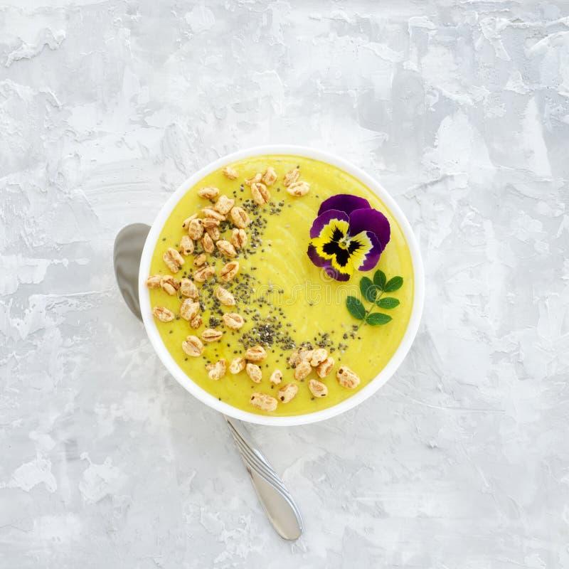 Le bol jaune de smoothie avec des graines de Chia, le blé d'air et la pensée fleurissent sur le fond concret images libres de droits