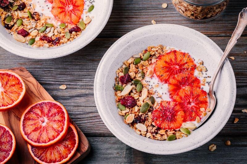 Le bol sain de petit déjeuner de granola faite maison avec du yaourt frais et le sang coupe en tranches des oranges image libre de droits