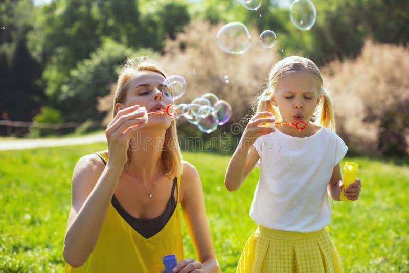 Le bolle di salto della mamma allegra appassiscono la figlia immagini stock libere da diritti