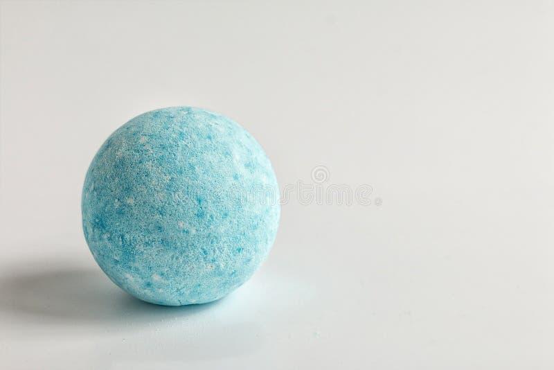 Le bombe blu fatte a mano romatic di schiumatura su fondo bianco Accessori della stazione termale del bagno Copi lo spazio per te immagini stock