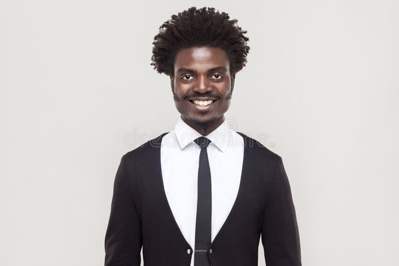 Le bonheur a bien habillé l'homme d'affaires Afro regardant l'appareil-photo, dent photographie stock libre de droits