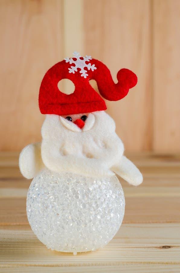 Le bonhomme de neige de jouet dans un chapeau rouge est tir lumineux grand sur un fond en bois photos stock