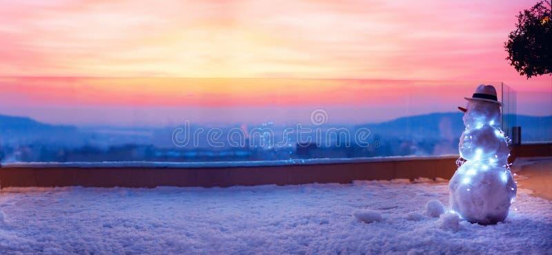Le bonhomme de neige mignon observant le soleil va vers le bas sur la terrasse de dessus de toit image libre de droits