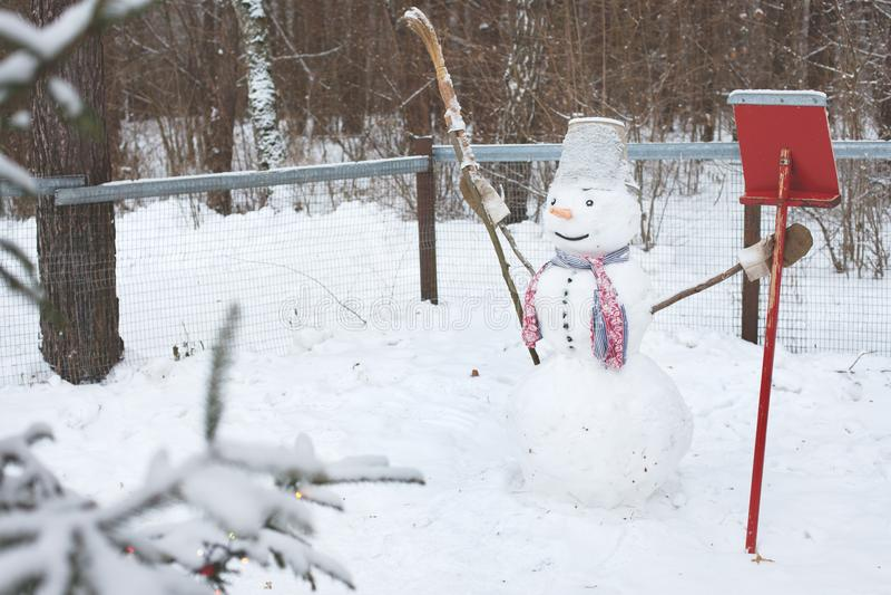 Le bonhomme de neige se tient dans la neige avec un balai et une pelle images stock