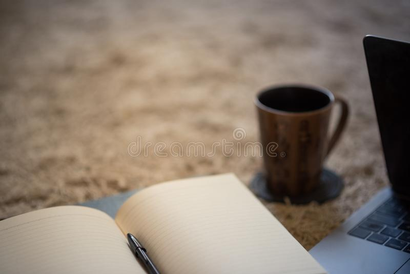 Le bord d'un journal ouvert de invitation avec la tasse et l'ordinateur portable de café, image libre de droits