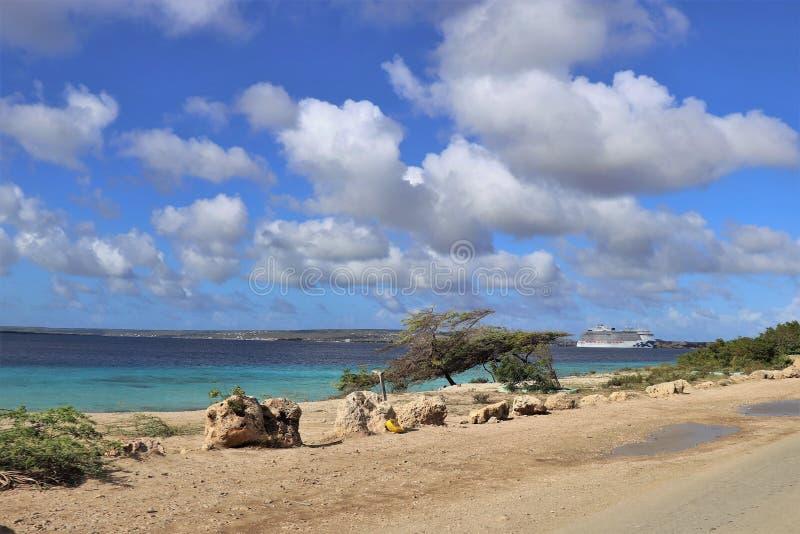 Le bord de l'océan avec les cieux bleus et un bateau de croisière se sont accouplés dans la distance image stock