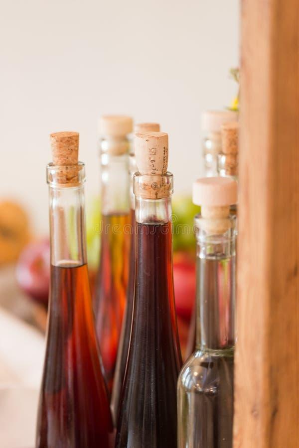 Le bottiglie d'annata strette con la casa hanno prodotto la vodka scura della prugna immagine stock libera da diritti