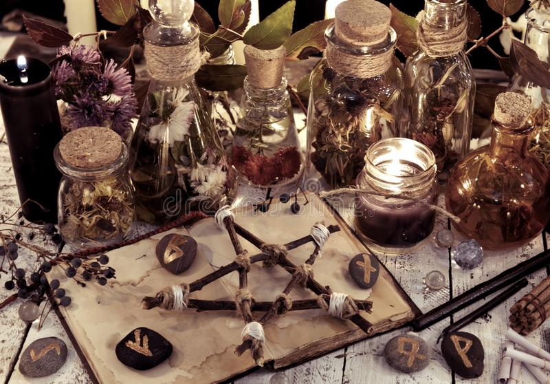 Le bottiglie della pozione, il pentagramma di legno, le candele nere e gli oggetti magici sulla strega presentano, immagine tonif immagini stock