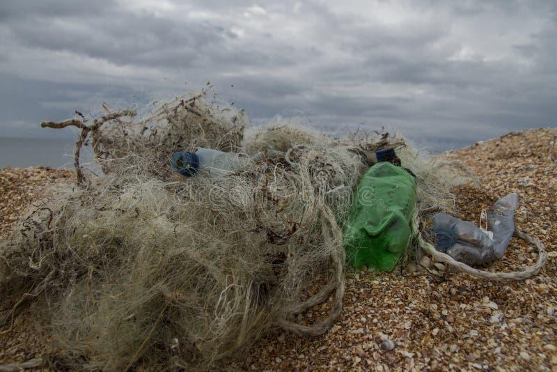 Le bottiglie di plastica e le reti da pesca inquinano la riva immagine stock libera da diritti