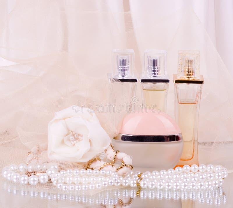 Le bottiglie di profumo, la rosa di bianco e le perle nuziali bordano fotografia stock libera da diritti