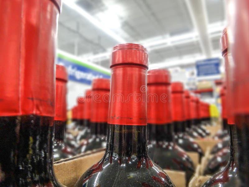 Le bottiglie di vino impilate sugli scaffali di legno hanno sparato la profondità limitata di immagine stock libera da diritti