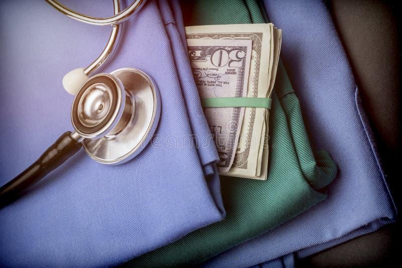 Le bouchon du dollar américain d'argent dans les soins vêtx, stéthoscope dessus photographie stock libre de droits