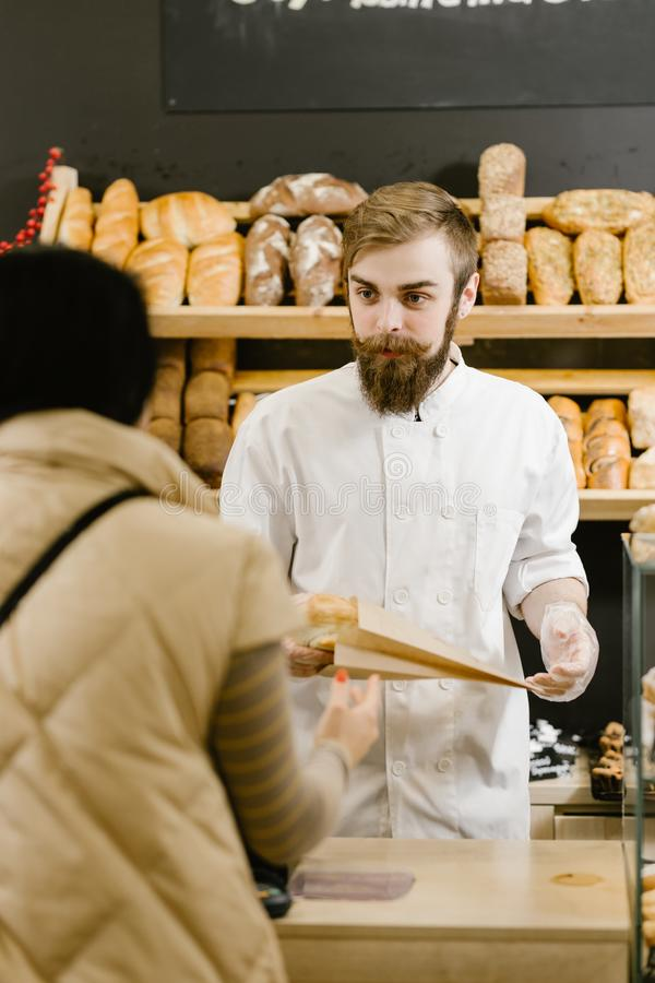 Le boulanger charismatique avec une barbe et une moustache donne un sac de papier de pain au client dans la boulangerie photo libre de droits