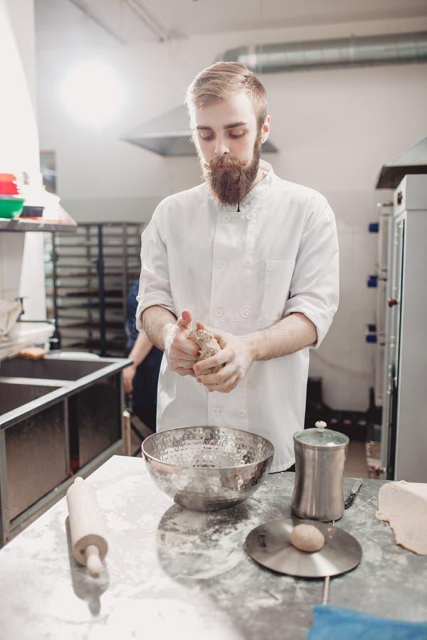 Le boulanger charismatique avec une barbe et une moustache malaxe la p?te sur la table dans la boulangerie photographie stock libre de droits