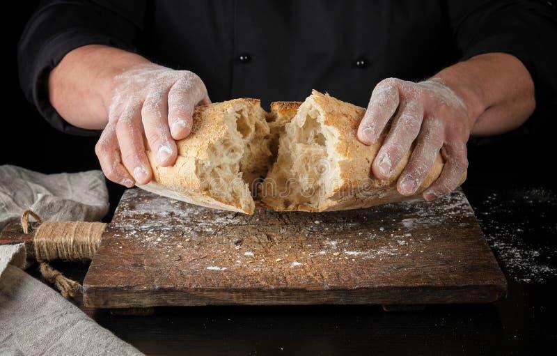 le boulanger dans l'uniforme noir a enfoncé la moitié d'un pain cuit au four entier photos stock