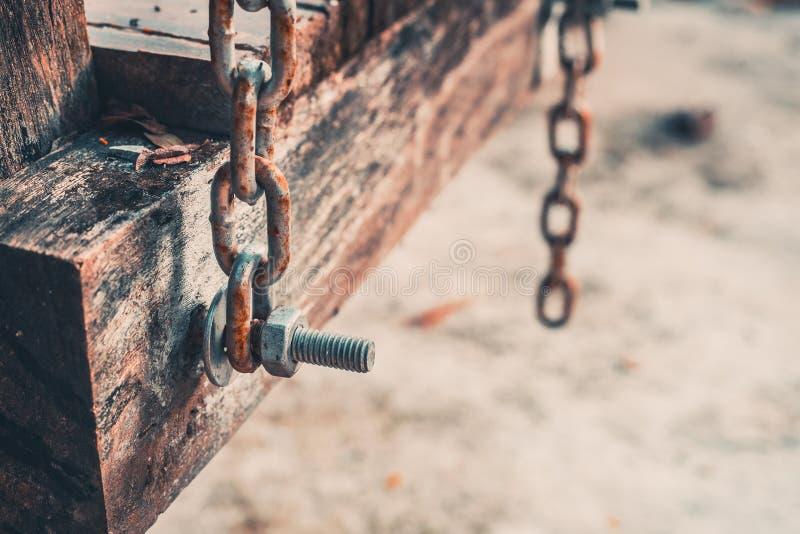 Le boulon sur la vieilles oscillation et chaîne en bois photo stock