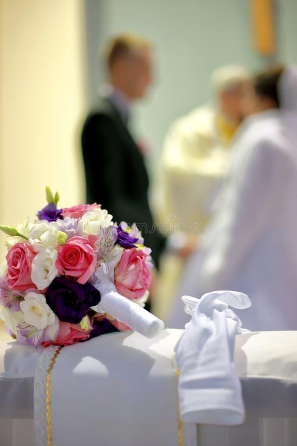Le bouquet de jeunes mariées à l'église sur le kneeler images stock