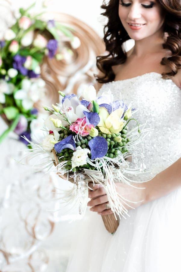 Le bouquet de jeunes mariées Une jeune mariée heureuse regardant son bouquet photos libres de droits