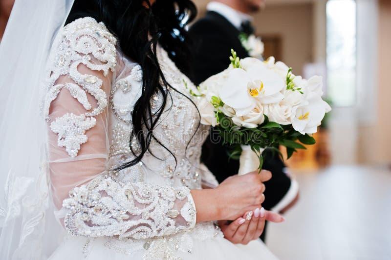 Le bouquet de mariage des orchidées blanches en main de la jeune mariée sur l'église cere photo libre de droits