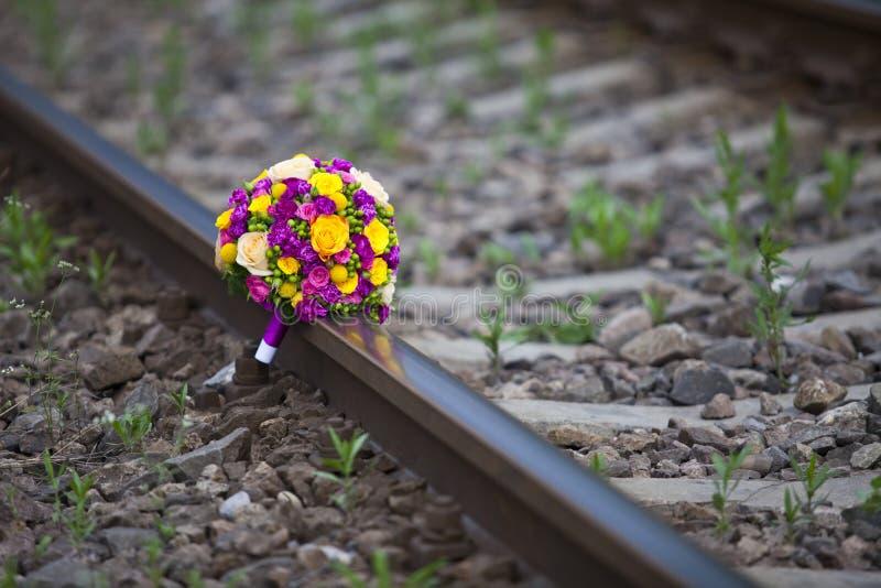 Le bouquet des fleurs s'est reposé sur le chemin de fer image stock