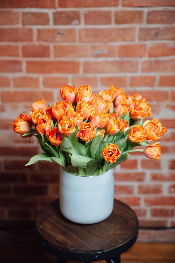 Le bouquet des tulipes oranges s'approchent du mur de briques photos stock