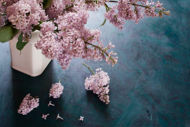 Le bouquet du lilas se tient dans le vase blanc et les inflorescences cassées se trouve sur le fond vert photographie stock libre de droits