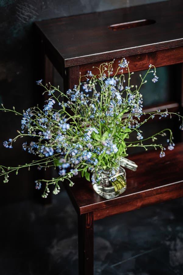 Le bouquet du myosotis des marais dans le petit pot en verre sur le tabouret en bois, fond fonc? image stock