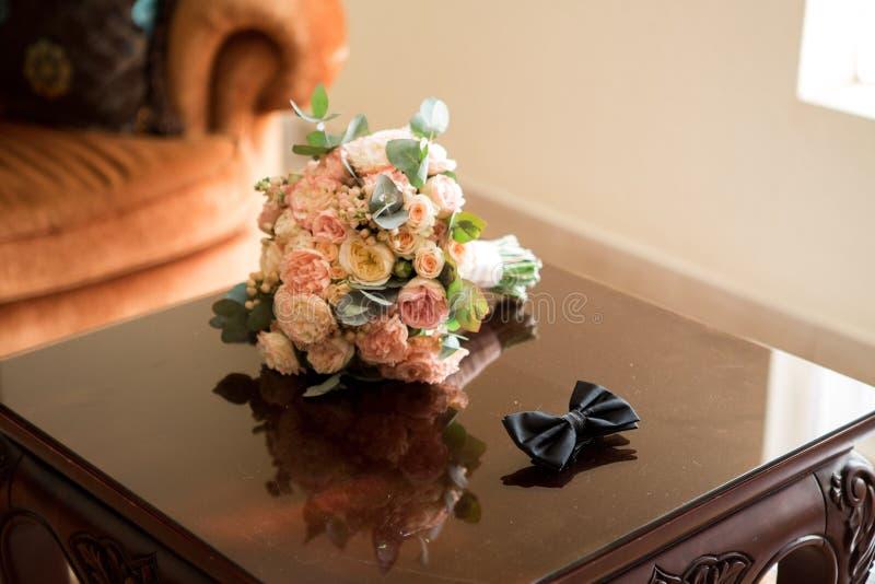 Le bouquet du ` s de jeune mariée et le noeud papillon du ` s de marié photos stock