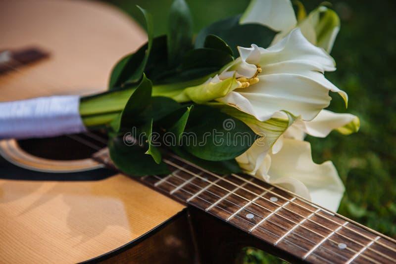 Le bouquet l'épousant blanc modeste se trouve sur la plate-forme de guitare photo libre de droits