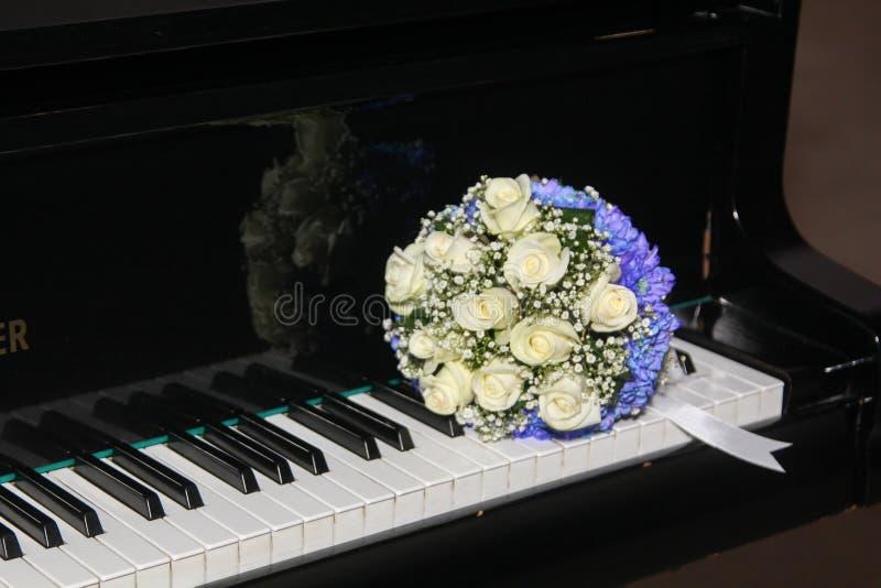 Le bouquet nuptiale des roses se trouve sur des clés de piano photos libres de droits
