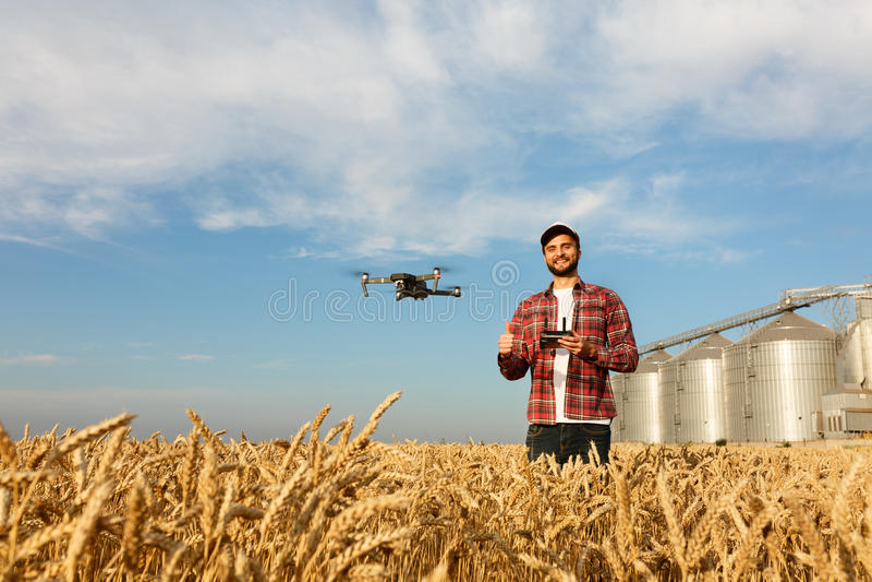Le bourdon plane devant l'agriculteur avec le contrôleur à distance dans des mains près de l'élévateur à grains Quadcopter vole p image libre de droits